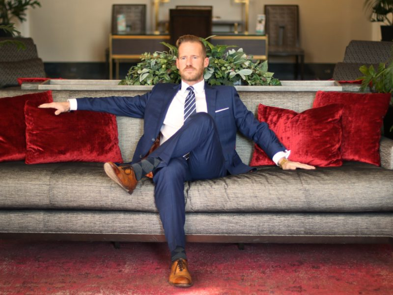 Jonathan Reid owner, Jeffrey Ives, sitting on a couch wearing a suit
