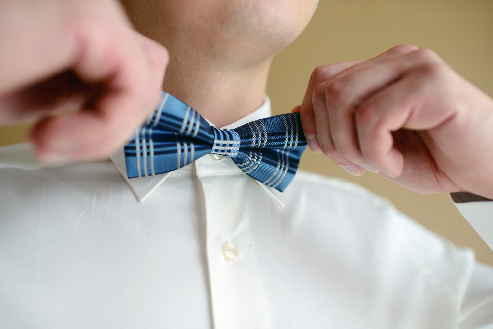 Man tying a blue bowtie