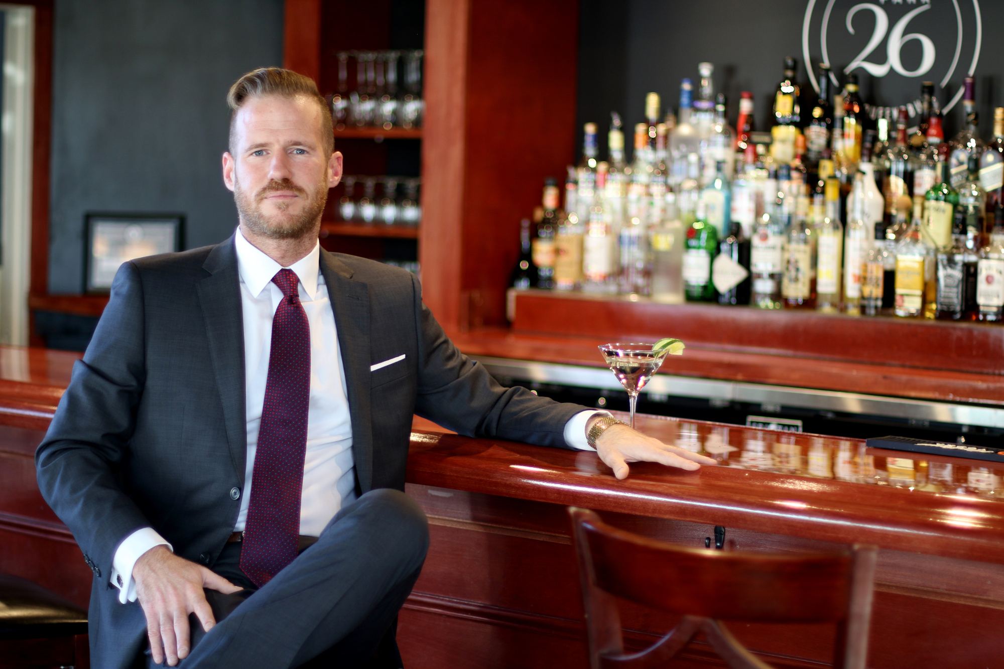Picture of Jonathan Reid owner, Jeffrey Ives, sitting at a bar in a suit