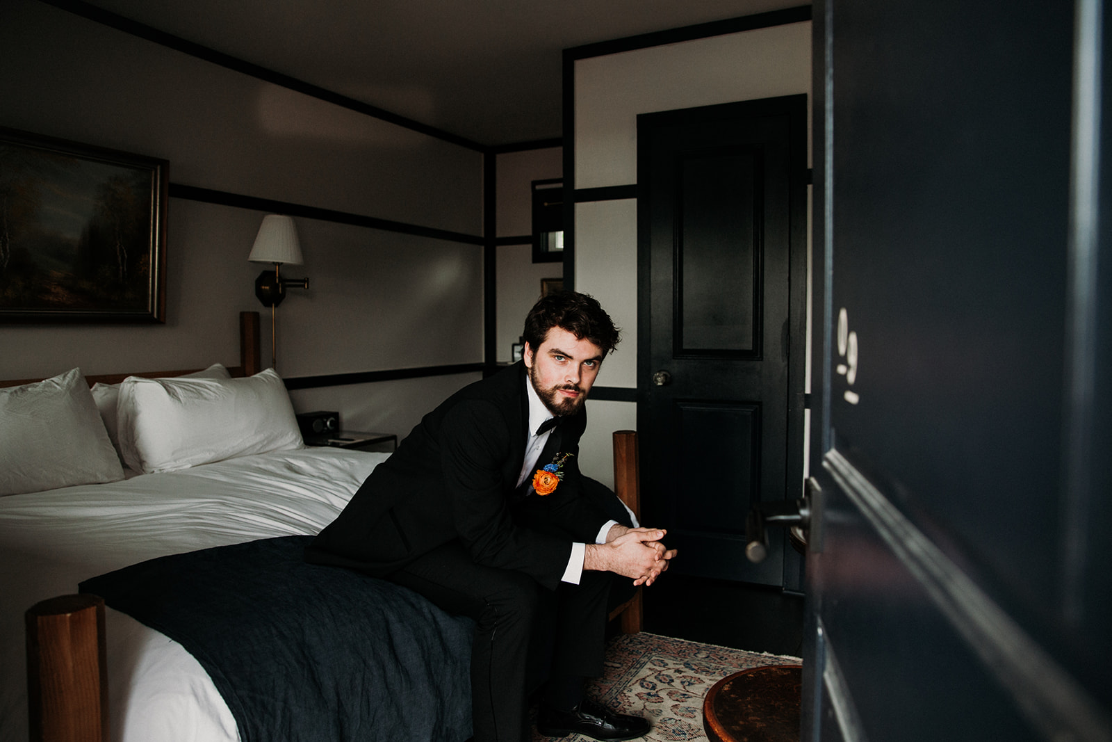 Groom in suit sitting on a bed